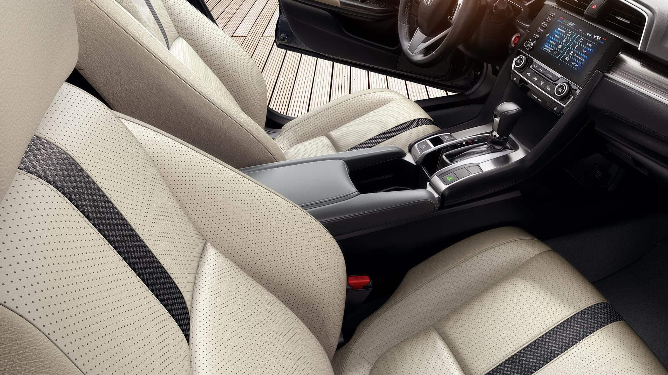 Vista del interior desde el lado del pasajero de los asientos delanteros del Honda Civic Touring Sedán2020 en Ivory Leather.