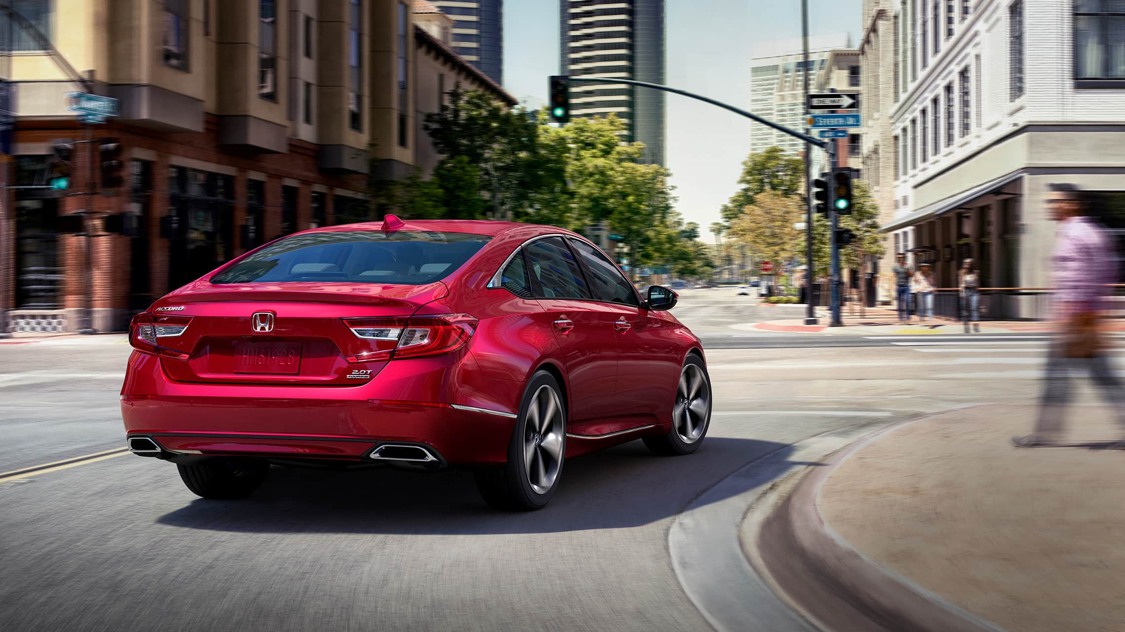 2020 Honda Accord Touring 2.0T in Radiant Red Metallic, making a turn at a downtown intersection.