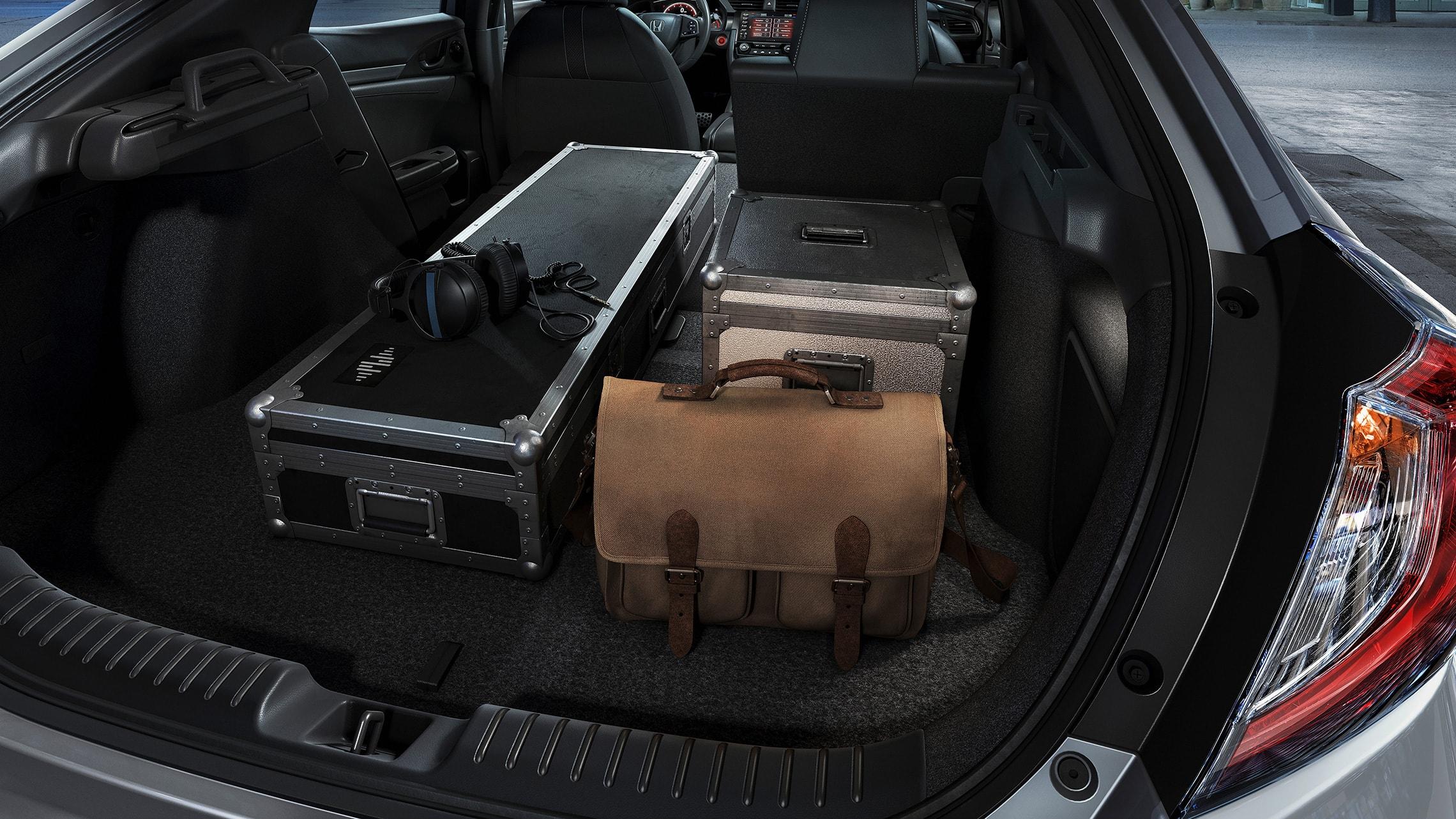 Varios artículos cargados en el espacio de carga del Honda Civic Sport Touring Hatchback 2021 con asientos traseros divididos y plegables 60/40.