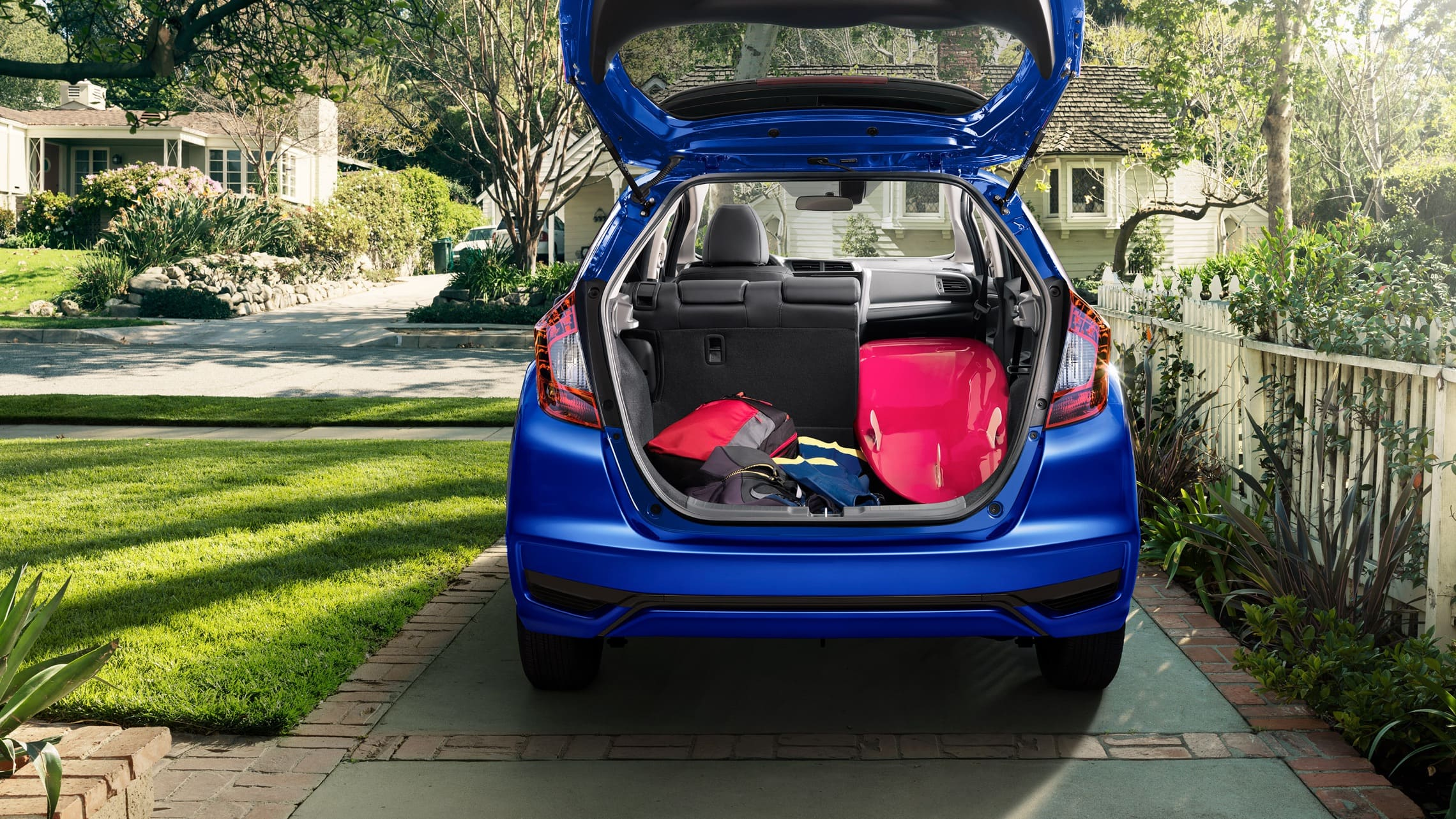 Rear of the 2020 Honda Fit EX-L in Aegean Blue Metallic with hatch open and surfboard in cargo area.