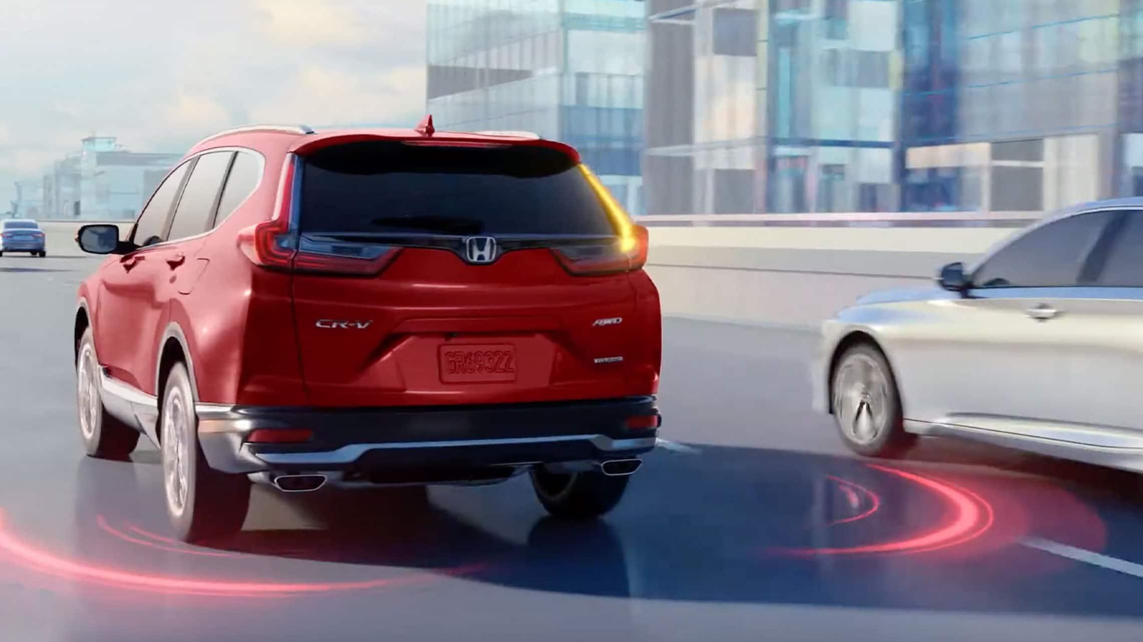 Vista trasera desde el lado del conductor de la Honda CR-V2021 en Radiant Red Metallic, conduciendo por una autopista, con una ilustración que muestra la característica del sistema de información de puntos ciegos.
