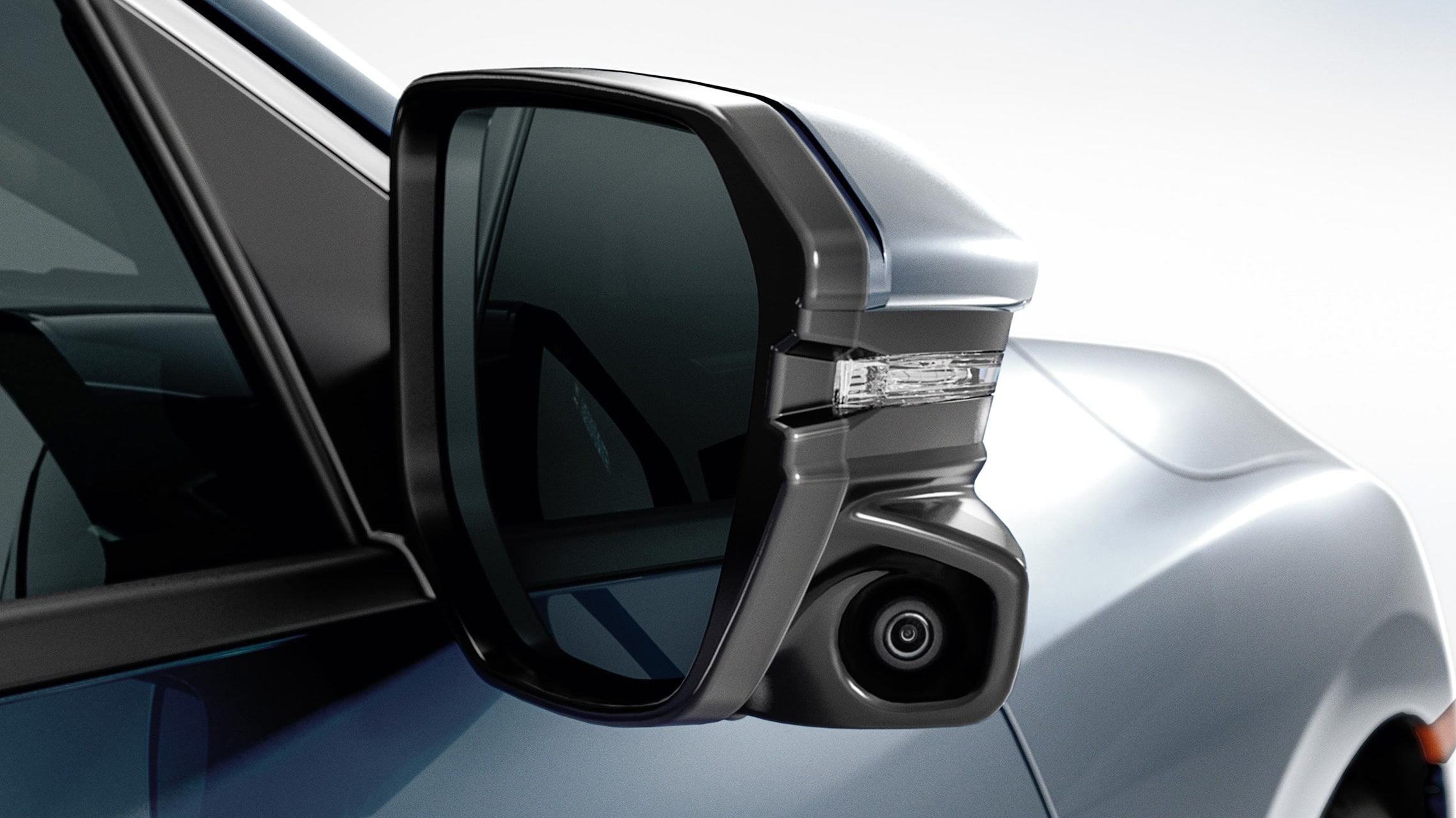 Detalle de la cámara Honda LaneWatch™ en el espejo del lado del pasajero del Honda Civic Touring Sedán2021 en Cosmic Blue Metallic.